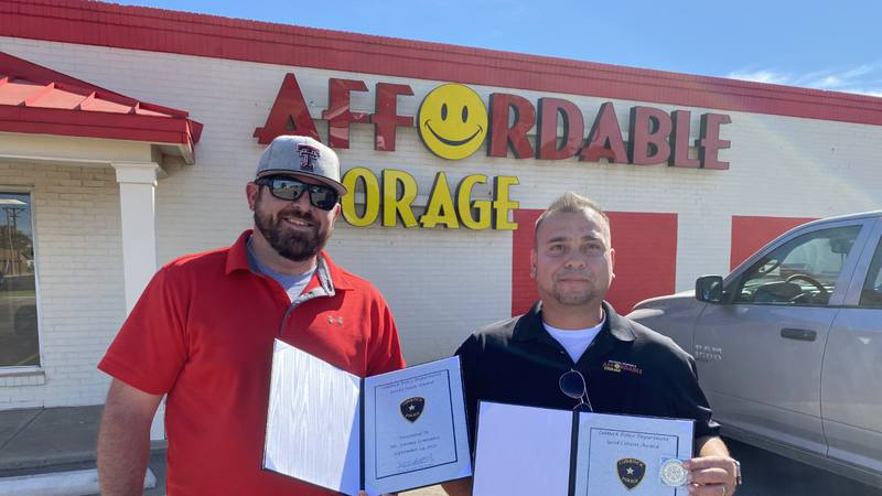 Jeremy Lowrance and Leonard Pena stand with their awards in front of Affordable Storage.