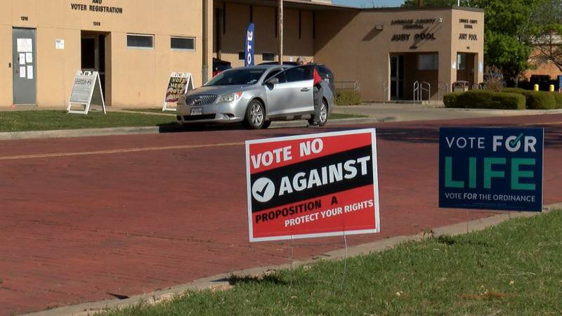 Signs outside the Lubbock County Elections Office try to persuade voters deciding on...