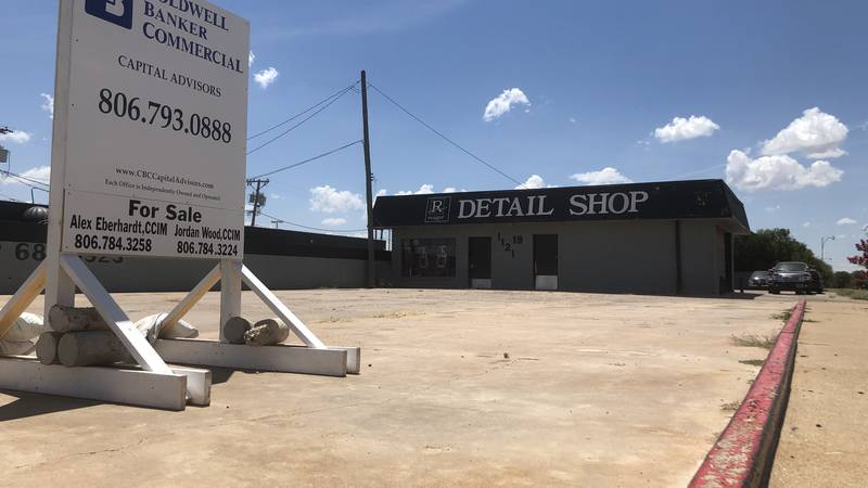 A realty company sign sits in front of a Reagor-Dykes Auto Group Detail Shop.