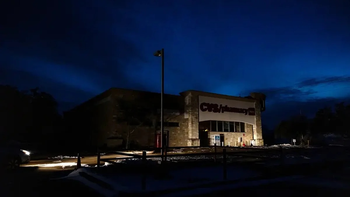 A CVS Pharmacy in South Austin is lit only by the lights of a parked car. Various parts...