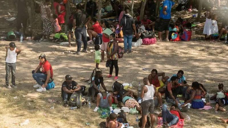 Asylum-seeking migrants rest under the International Bridge in Del Rio between Mexico and the...