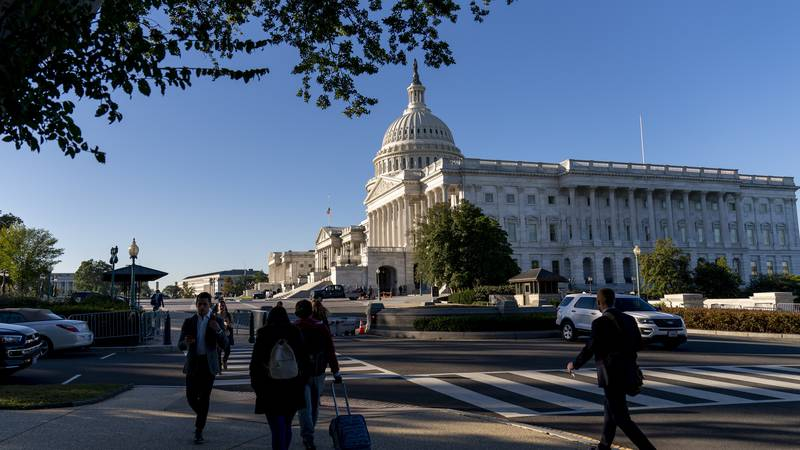 People walk by the U.S. Capitol in Washington, Tuesday, Oct. 19, 2021. A centerpiece of...