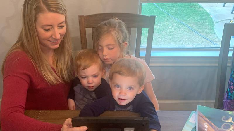 Hall Family looking at daughter's daily school work
